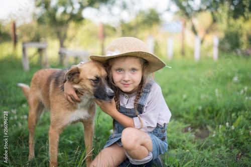Leinwanddruck Bild Girl and dog playing during autumn gardening in yard
