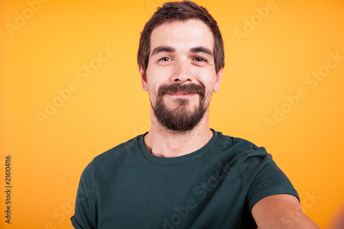 Foto Murales Close up selfie portrait of happy smiling man isolated on yellow background