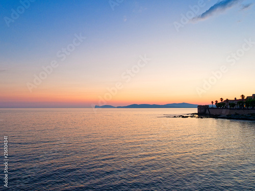 Fotobehang Zee zonsondergang View of the promenade and the old walls of alghero. Alghero, Sardinia, Italy.
