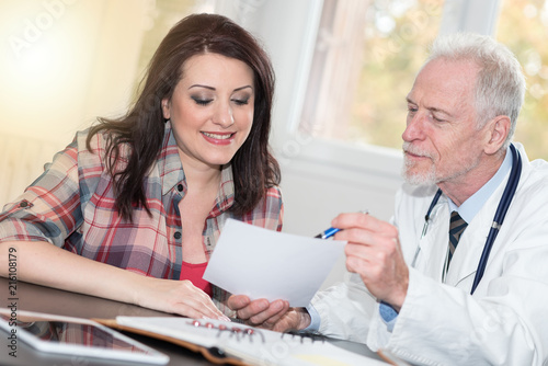 Senior doctor giving prescription to female patient, light effect