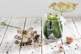 Preserved cucumbers in glass jar with dill and garlic on  table - 216109945