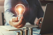 Leinwanddruck Bild - businessman hand holding lightbulb with using laptop and money stack in office. idea saving energy and accounting finance concept