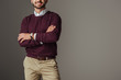 cropped view of man posing in burgundy sweater with crossed arms, isolated on grey