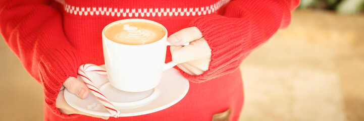 Girl holding a cappuccino cup with candy cane. Concept of Christmas holiday. Holiday background © Ekaterina_Molchanova