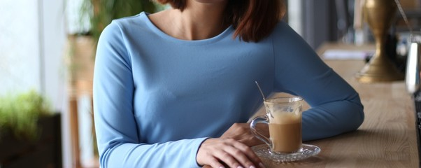 girl in blue dress sits at a bar counter and drinks coffee.expectation of meeting. morning breakfast © Skripnik Olga