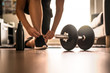 Leinwanddruck Bild - Morning workout routine in home gym. Fitness motivation and muscle training concept. Man in sneakers tying shoelaces in sunlight. Athlete starting exercise with dubbell weight.