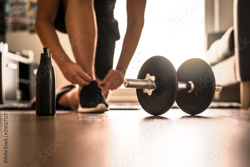 Leinwanddruck Bild Morning workout routine in home gym. Fitness motivation and muscle training concept. Man in sneakers tying shoelaces in sunlight. Athlete starting exercise with dubbell weight.