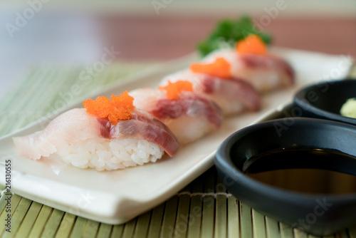 Foto Spatwand Sushi bar Hamachi sushi on white plate along with Japanese sauce and green leaf decoration, Japanese food, close up at sushi ..