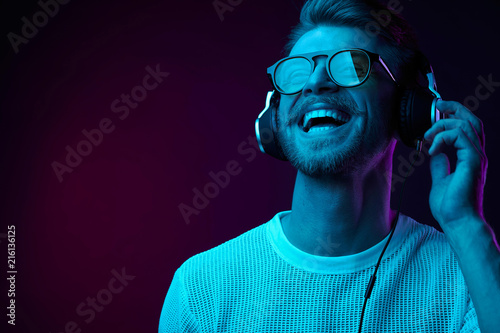 Neon portrait of bearded smiling man in headphones, sunglasses, white t-shirt. Listening to music - 216136125