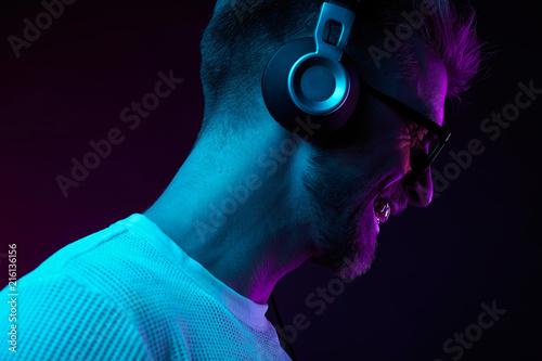 Neon portrait of bearded smiling man in headphones, sunglasses, white t-shirt. Listening to music - 216136156