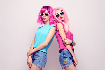 Two Girl with Pink Fashion Hairstyle Posing in Studio. Young Hipster Model Woman in Stylish Outfit, Trendy Sunglasses. Cool Crazy Friends, Cheeky Emotion. Sweet colors © evgenij918