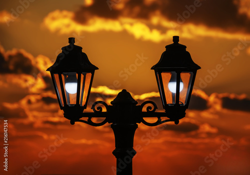 Street lamp at sunset sky background