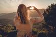Leinwandbild Motiv Frau beim Sonnenuntegang mit Herz