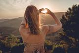 Frau beim Sonnenuntegang mit Herz