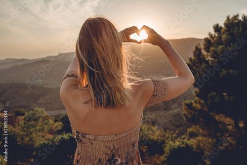 Frau beim Sonnenuntegang mit Herz - 216153384