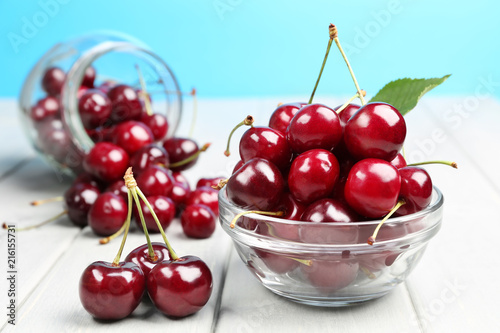 Foto Spatwand Kersen bowl and bottle with ripe cherries on the table
