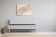 Quadro Poster above grey settee in minimal living room interior with copy space and flowers. Real photo
