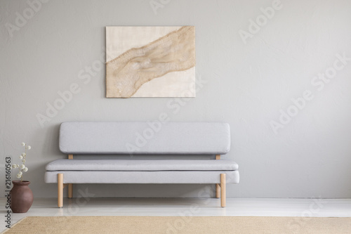 Poster above grey settee in minimal living room interior with copy space and flowers. Real photo