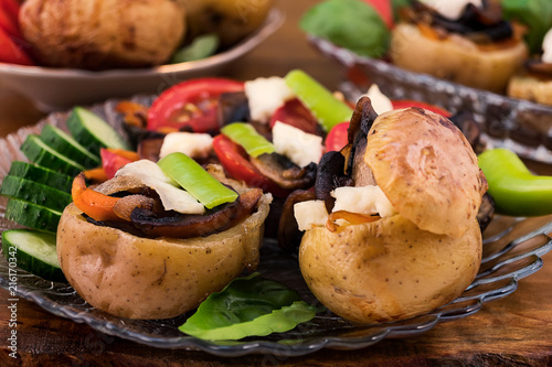 Baked with peel in the oven potatoes, stuffed with fried sliced mushrooms with white soft cheese, laid on a glass plate with slices of tomatoes, cucumbers.