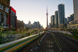 Train in downtown of Toronto with highrise buildings and CN Tower at sunset