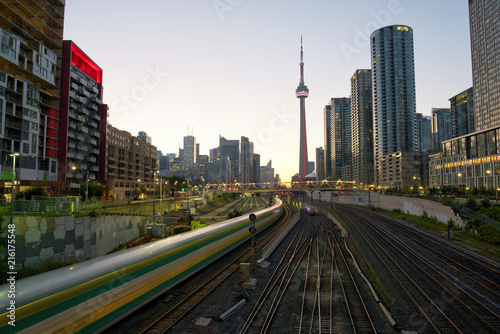 Canvas Toronto Train in downtown of Toronto with highrise buildings and CN Tower at sunset