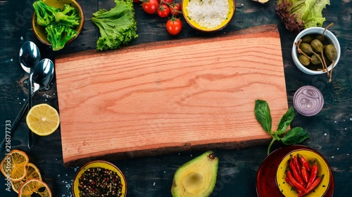 Foto Spatwand Kersen Cooking. Cherry tomatoes, lettuce, wooden board and spices. Top view. Free space for your text.
