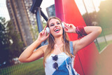 Portrait of smiling young woman listening music outdoors at urban basketball court