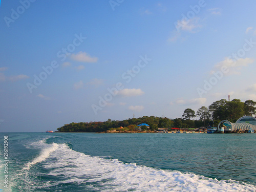 Plexiglas Tropical strand splashes of waves from a motor boat, beautiful sunset landscape