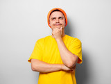 Young handsome man in yellow t-shirt and orange hat on white background