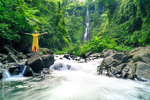 Fotobehang Bali Woman in yellow dress at the Sekumpul waterfalls in jungles on Bali island, Indonesia