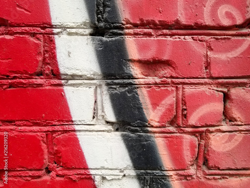Fragment of colored abstract brick wall paint in red, black and white colors - 216209320