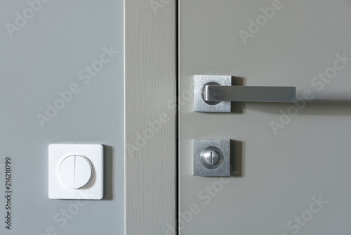 A Metal Handle And A Lock On The Gray Interior Door And A White Switch On