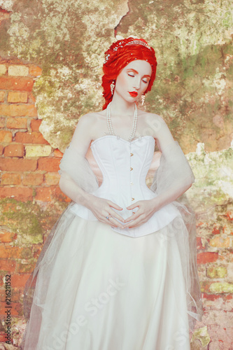 Young victorian princess with hairstyle in castle. Fabulous rococo queen in white historic dress against backdrop of old stone wall. Doll in corset. Victorian historic imitation countess in palace.