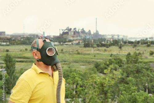 Man wearing gas mask against of industrial factory.