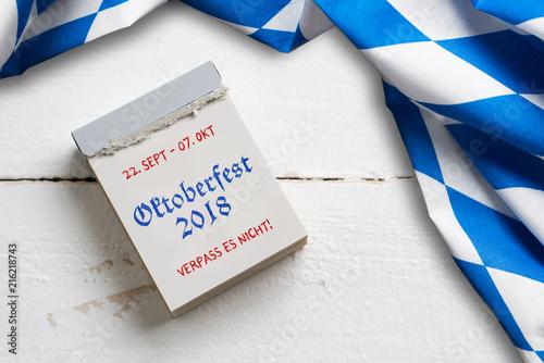 Tischtuch mit bayrischem Rautenmuster auf Holzuntergrund und Abreißkalender mit Aufschrift