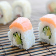 Sushi rolls lies on a bamboo straw serwing mat. Traditional Asian food. Shallow depth of field