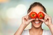 Leinwanddruck Bild - Beautiful laughing woman holding two ripe tomatoes
