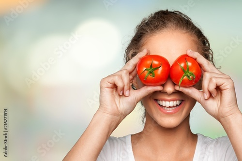 Beautiful laughing woman holding two ripe tomatoes - 216221914