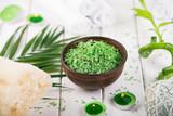 Spa. Green herbal spirulina salt in ceramic bowl, spa towels, candles and bamboo