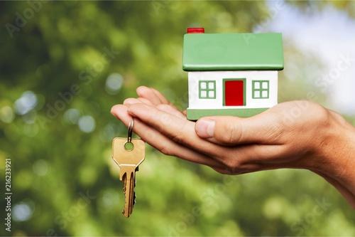 Leinwanddruck Bild Businessman Holding House Model and Keys