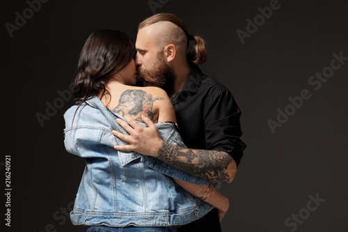 Attractive young couple with tattoos kissing on dark background