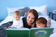 Leinwandbild Motiv Young nanny reading book to cute little children on bed
