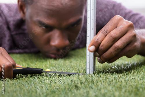 Foto Murales Man Cutting The Measured Grass With Scissor