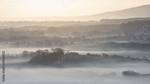 Canvas Wit Stunning foggy English rural landscape at sunrise in Winter with layers rolling through the fields