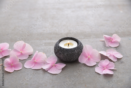 Plexiglas Spa Many Pink hydrangea petals with candle on gray background