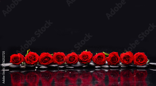 Plexiglas Spa row of red rose and wet stones-black background