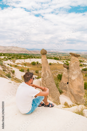 Canvas Wit young man on the hill watching the moon landscape of Cappadocia fairytale mushroom hills
