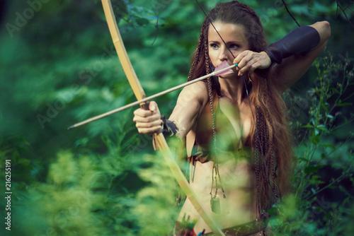 Leinwandbild Motiv Girl huntress shoots from a classic wooden bow