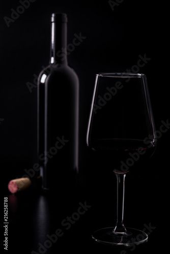 Silhouette of red wine glass with bottle behind and the cork next to it isolated on black dark background with soft reflections and beautiful shadows. Shallow depth of field