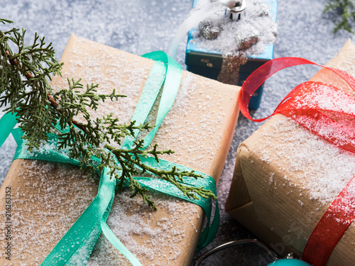 Christmas new year wrapped gift box with ribbon and snow. Pine cones and decorations. Winter festive background